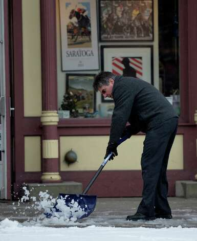 A person removes slush from the front of Frame Crafters on Broadway Wednesday afternoon, March 12, 2014, as a late winter storm hits  Saratoga Springs, N.Y. (Skip Dickstein / Times Union) Photo: SKIP DICKSTEIN / 00026108A