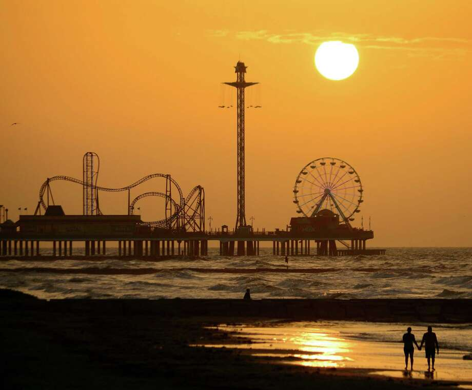 A golden-dawn walk along the beach in Galveston may bring a sunrise view of the Pleasure Pier in its dormancy, before the advancing day turns its family-friendly rides, midway games, restaurants and retail shops into a bustling hive of activity. Photo: Courtesy Galveston CVB