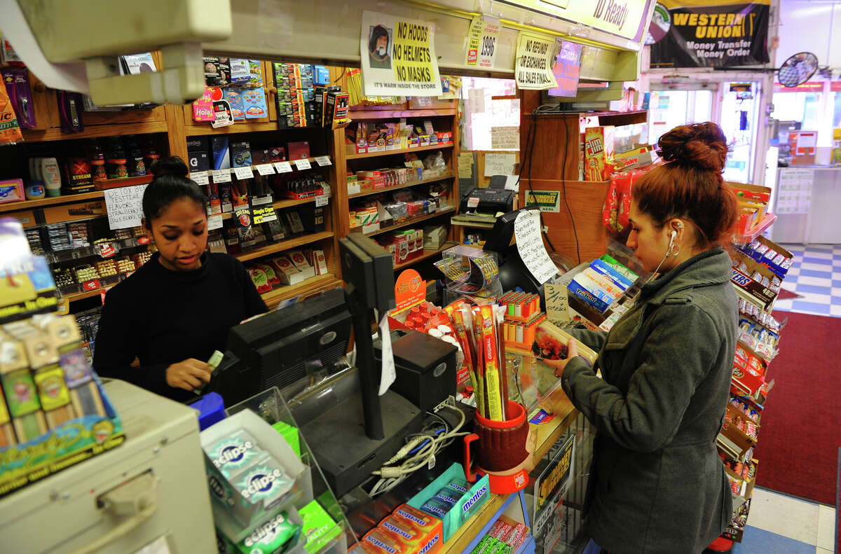 Jasmine Chinnis, at register, sells e-cigarette oil refills to a customer at Martin's News & Cigarette Outlet in Stratford, Conn. on Wednesday March 12, 2014.