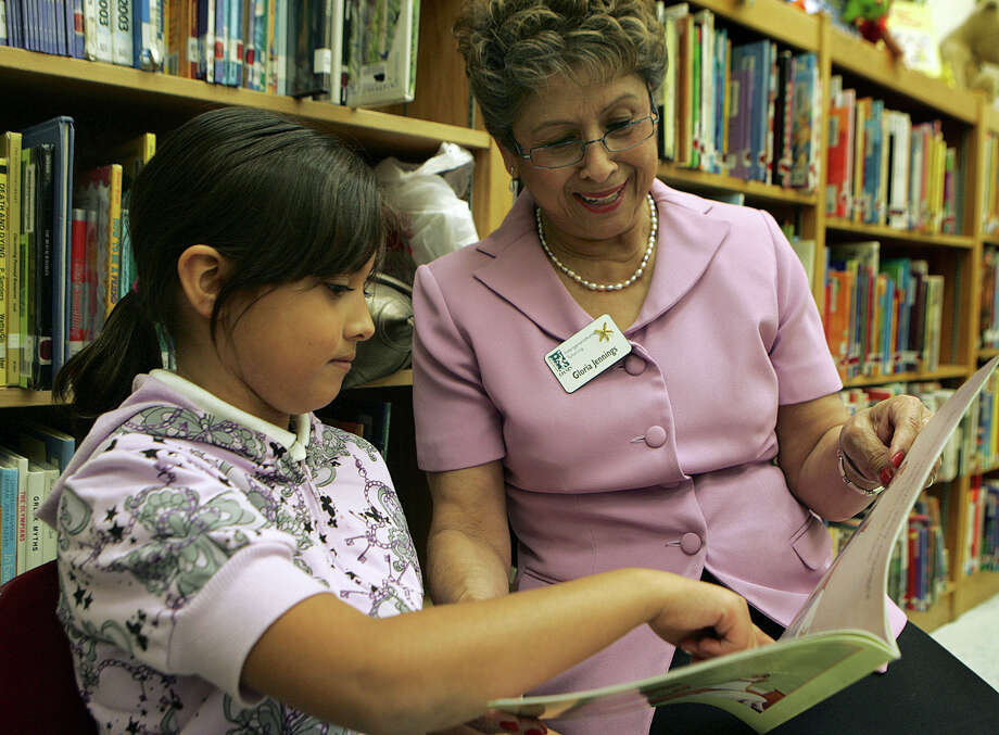 Gloria Salas-Jennings, a volunteer with the Oasis Tutoring Program, reads to a student. Jennings encourages adults to volunteer to read to children. Photo: Express-News File Photo / KGEIL@EXPRESS-NEWS.NET