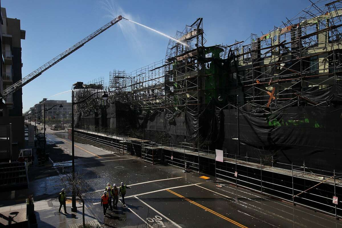 Firefighters continue to work on completely putting out a fire at the scene of a five alarm fire that broke out Tuesday afternoon in an unfinished apartment complex in Mission Bay March 12, 2014 in San Francisco, Calif.