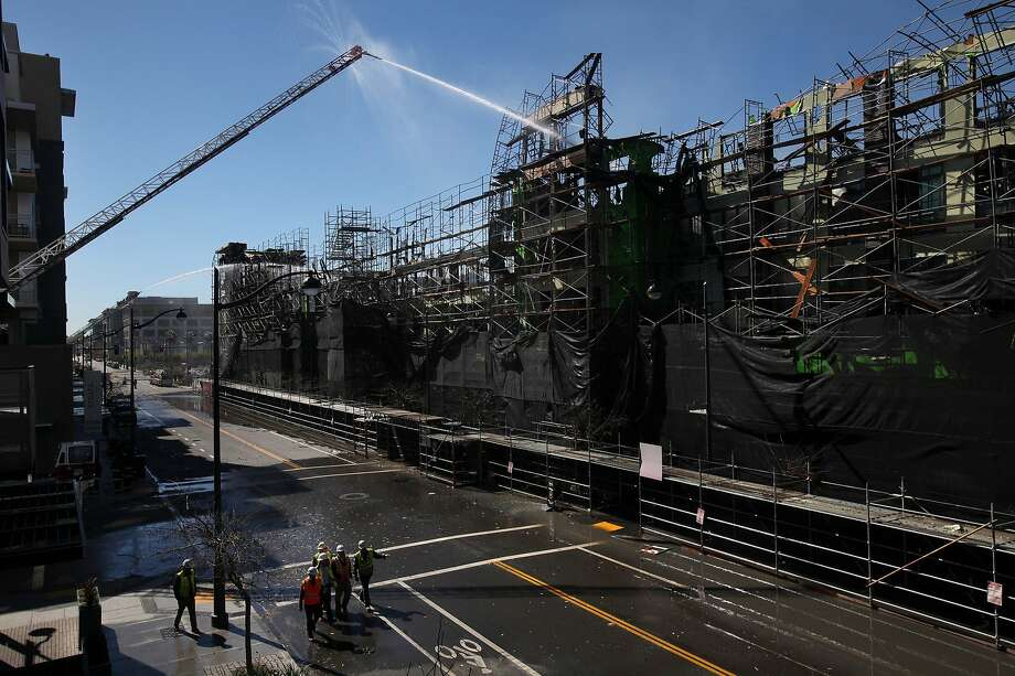 Firefighters continue to work on completely putting out a fire at the scene of a five alarm fire that broke out Tuesday afternoon in an unfinished apartment complex in Mission Bay March 12, 2014 in San Francisco, Calif. Photo: Leah Millis, The Chronicle