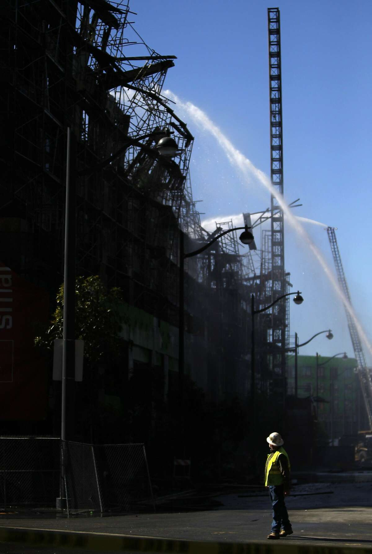 A construction worker watches as firefighters continue to put out a fire at the scene of a five alarm fire that broke out Tuesday afternoon in an unfinished apartment complex in Mission Bay March 12, 2014 in San Francisco, Calif.