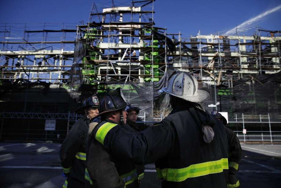 Firefighters talk in a group as water is continued to be sprayed onto the Mission Bay apartment building construction site the day after a five-alarm fire on Wednesday, March 12, 2014,  in San Francisco, Calif. Photo: Lea Suzuki, The Chronicle
