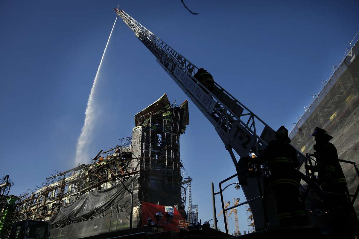 Firefighters continue to pour water onto the Mission Bay apartment building construction site the day after a five-alarm fire on Wednesday, March 12, 2014, in San Francisco, Calif.