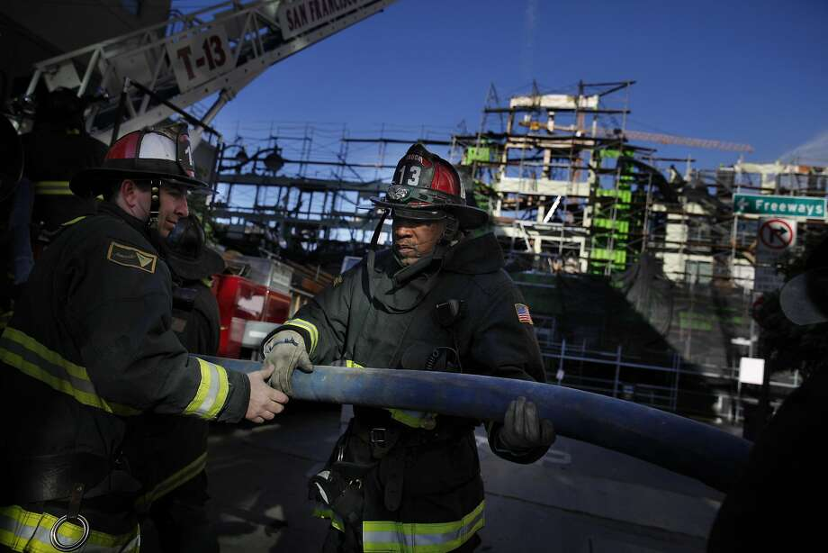 Firefighters move a hose in front of the Mission Bay apartment building as water continues to be sprayed on the construction site the day after a five-alarm fire on Wednesday, March 12, 2014,  in San Francisco, Calif. Photo: Lea Suzuki, The Chronicle