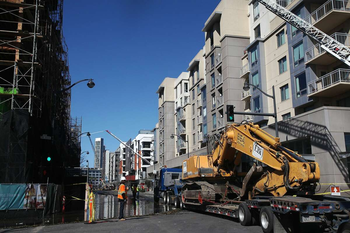A demolition machine is driven into the scene of a five alarm fire that broke out Tuesday afternoon in an unfinished apartment complex in Mission Bay March 12, 2014 in San Francisco, Calif.