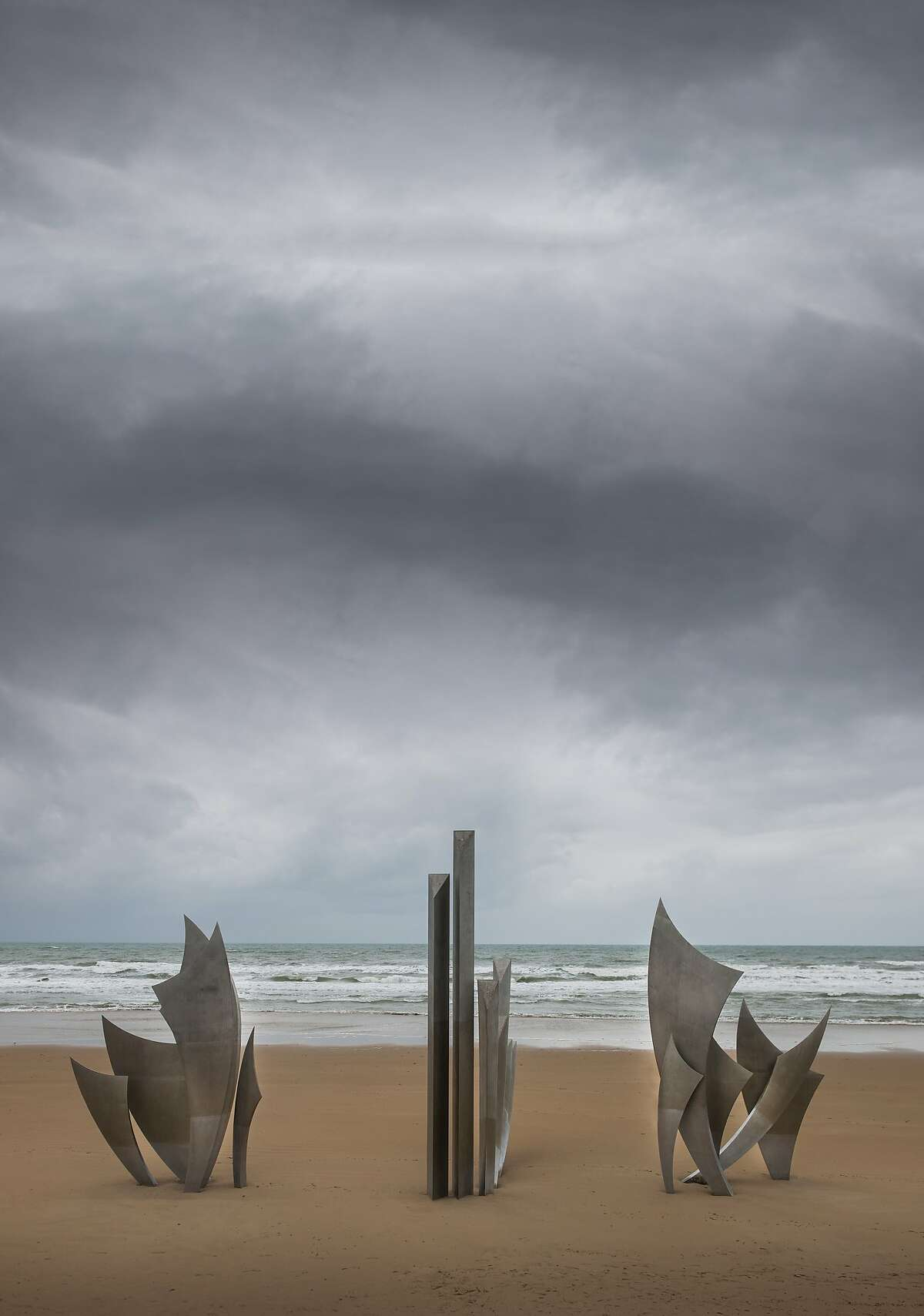 """The sculpture """"Les Braves"""" by Anilore Banon honoring the soldiers that landed on Omaha Beach on D Day and the days that followed, The sculpture has three elements, Wings of Hope, Rise, Freedom! and Wings of Fraternity. Sculpture - Les Braves - Omaha Beach"""
