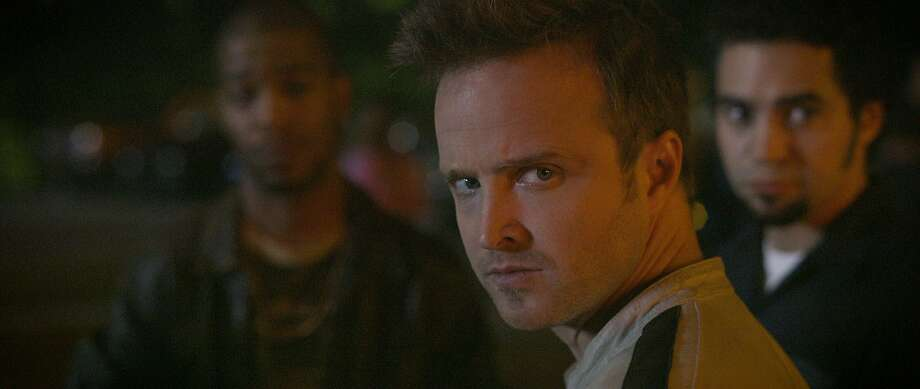 Tobey Marshall (Aaron Paul, center) with Benny (Scott Mescudi, left) and Joe Peck (Ramon Rodriguez) are featured in this scene in DreamWorks Pictures' 'Need for Speed,' an exciting return to the great car culture films of the 1960s and '70s that tap into what makes the American myth of the open road so enticing. Photo: Walt Disney Pictures