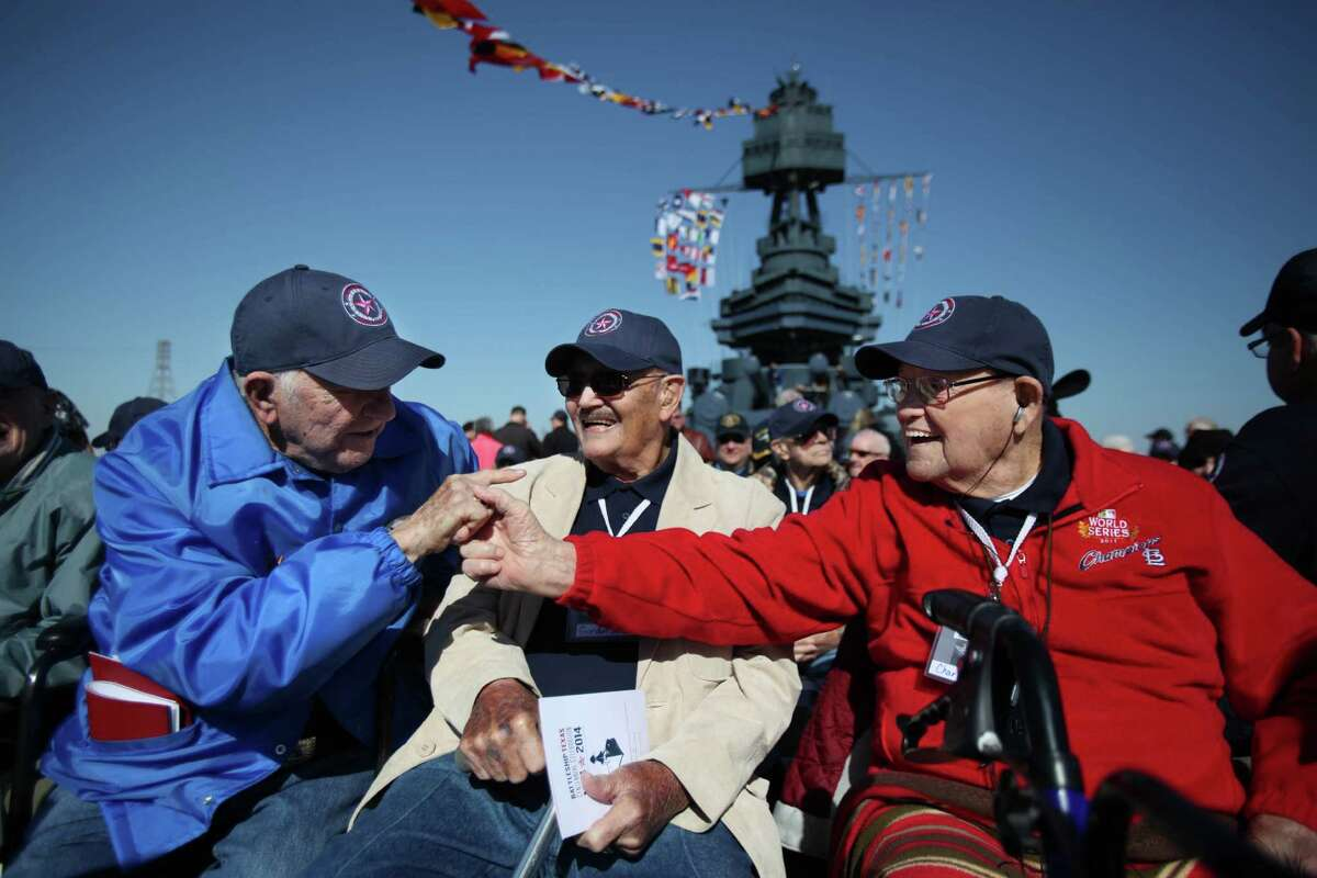 WWII veterans Ed Borowski, left, Gordon Jones and Charles Birlew, right, greet each other Wednesday aboard the USS Texas during the Crew Reunion and Centennial Commissioning Celebration at the San Jacinto Battleground.