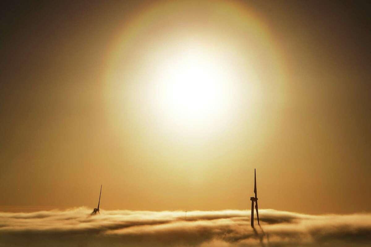 Fog envelops two 285-foot-tall wind turbines at the BP Sherbino Mesa II wind farm in West Texas.