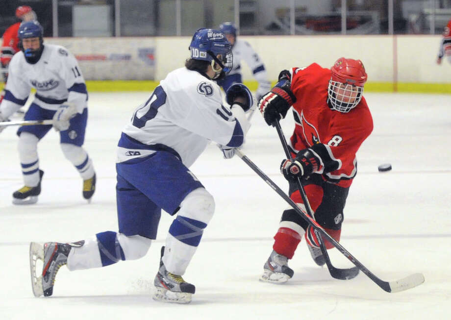 At right, Mark Schmeiler (#8) of Greenwich gets his shot blocked by Darien's Jack Massie (#10) during the CIAC Division I boys ice hockey playoff game between Greenwich High School and Darien High School at Darien Rink in Darien, Conn., Wednesday, March 12, 2014. Photo: Bob Luckey / Greenwich Time