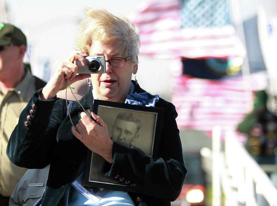 Cathleen Sain Turick carries a photo of her father WWII veteran Clyde Sain as she boards to the warship for the private Crew Reunion in celebration of the the Battleship Texas Centennial on March 12, 2014, in Houston. Photo: Mayra Beltran, Houston Chronicle / © 2014 Houston Chronicle