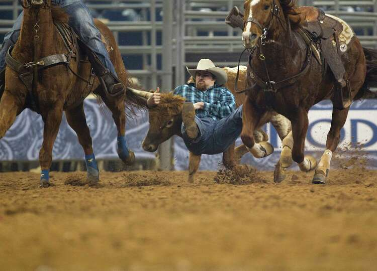 Jason Thomas takes down a steer in the Steer Wrestling event during the second round of the Rodeo Ho