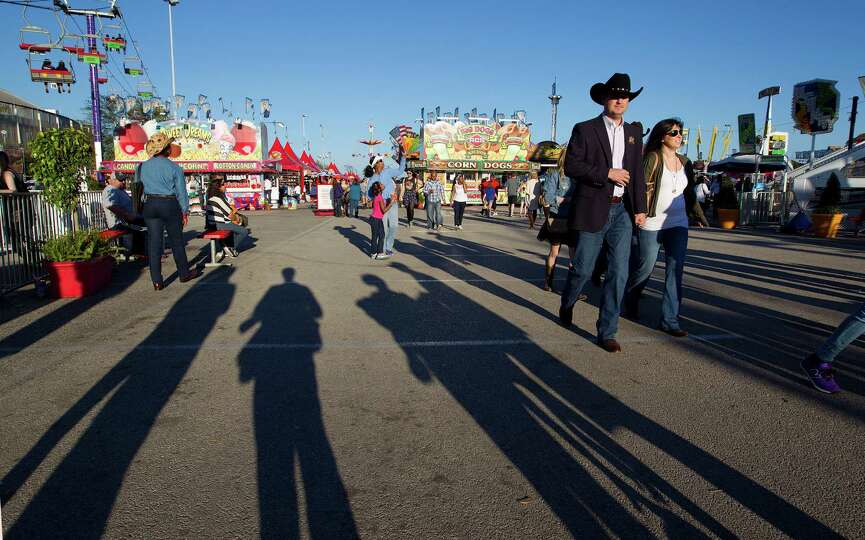Houston Livestock Show and Rodeo attendees walk through the carnival area in Reliant Park Tuesday, M
