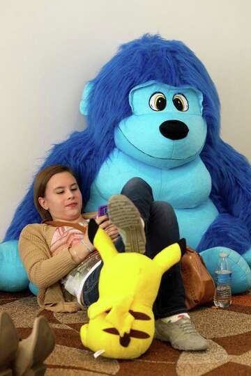 Comfortable leaning on stuffed animals her brother won, Kailey Starr, 16, texts on her cell phone wh