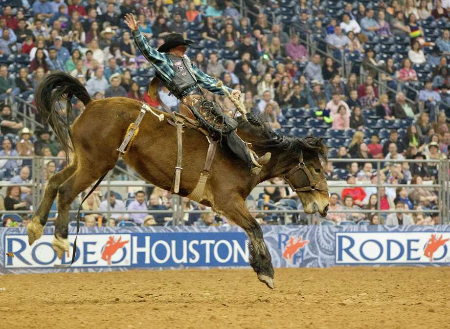 Rusty Wright, 18, wins the Saddle Bronc Riding event with riding the horse named Iron Maiden during the final round of the BP Super Series lll Rodeo Houston at Reliant Stadium Wednesday, March 12, 2014, in Houston. Photo: Johnny Hanson, Houston Chronicle / © 2014  Houston Chronicle