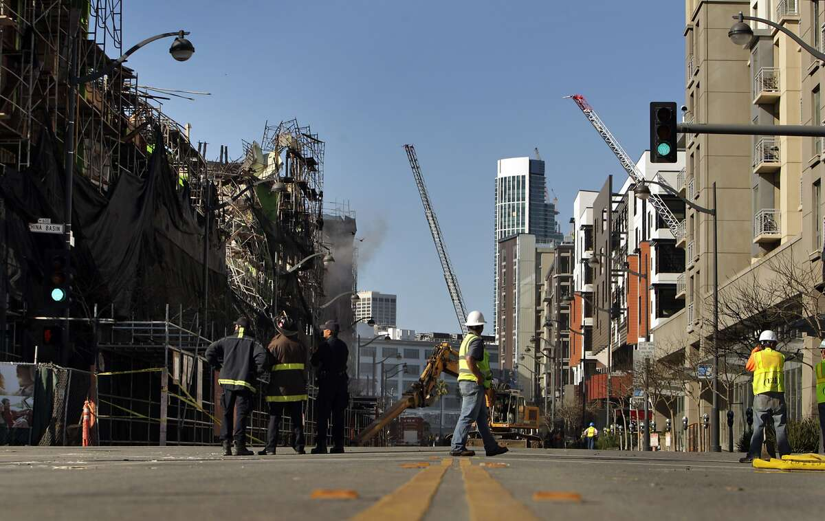 Firefighters and construction crews monitor the scene in San Francisco, Calif., on Wednesday, March 12, 2014, after a multi-alarm fire destroyed new construction apartments the day before. The Mission Bay neighborhood has undergone a major transformation that includes housing and commercial space in multi-story buildings around bio tech and business developments.