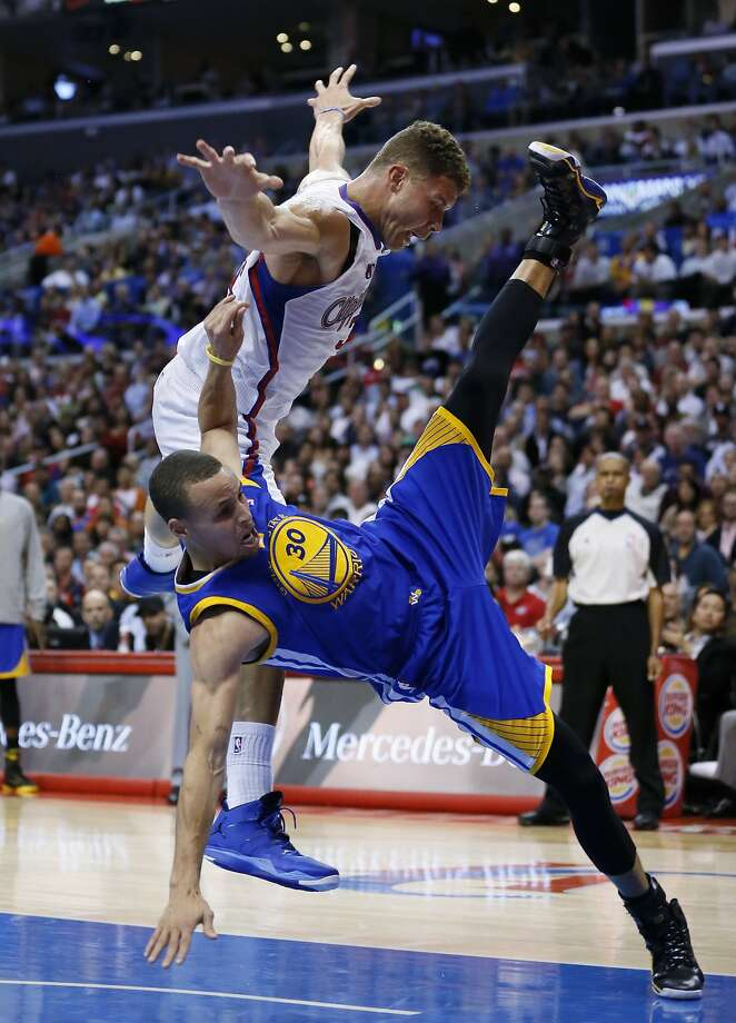 The Clippers' Blake Griffin (left) is fouled by Stephen Curry on a second-half drive. Photo: Danny Moloshok, Associated Press