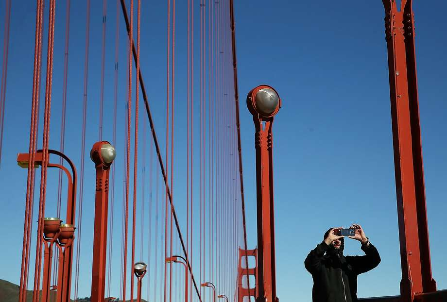 SAN FRANCISCO, CA - MARCH 12:  A visitor takes a photograph while walking on the Golden Gate Bridge on March 12, 2014 in San Francisco, California.  A long debated suicide barrier on the Golden Gate Bridge could be one step closer to  reality after Caltrans and the regional Metropolitan Transportation Commission have indicated that they will be willing to contribute $44 million toward putting giant nets under the span of the bridge. The Golden Gate Bridge district would need to invest $12 million in toll money to cover the remaining cost. Over 1,500 people committed suicide by jumping from the iconic bridge since it opened in 1937. 46 people jumped to their death in 2013.  (Photo by Justin Sullivan/Getty Images) Photo: Justin Sullivan, Getty Images