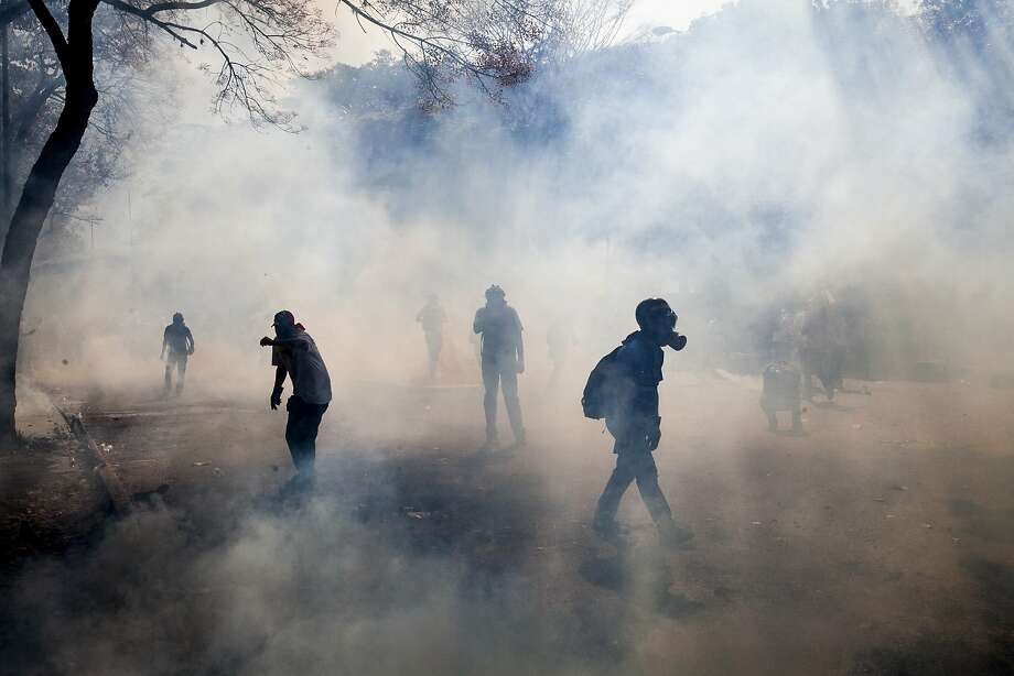 Demonstrators walk through a cloud of tear gas fired by the Bolivarian National Police during clashes in Caracas, Venezuela, Wednesday, March 12, 2014. A month of student-led demonstrations in a number of Venezuelan cities has left at least 25 people dead, according to the government. Venezuelans fed up with inflation that reached 56 percent last year, long lines for buying some items at grocery stores and one of the highest homicide rates in the world have joined students in protesting against the government. (AP Photo/Alejandro Cegarra) Photo: Alejandro Cegarra, Associated Press