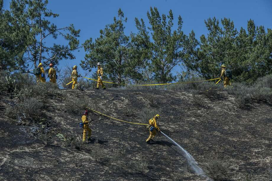 Firefighters spray water on a burned area during efforts to control a brush fire in Brea, Calif. on Wednesday, March 12, 2014. The fire began around 12:40 p.m. after a car lost its wheel, but no structures were threatened, according to the Brea Police Department. (AP Photo/The Orange County Register, Bruce Chambers) Photo: Bruce Chambers, Associated Press