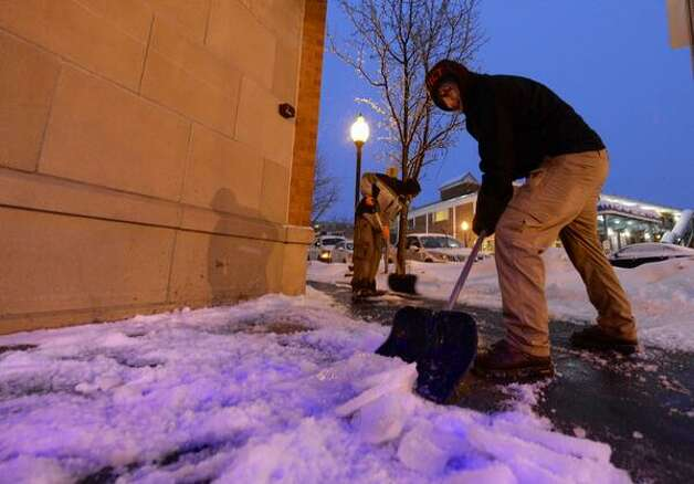 Robi Henry and Ryan Aubin chip away at the ice-crusted snow on Broadway in Saratoga Springs. (Skip Dickstein / Times Union)