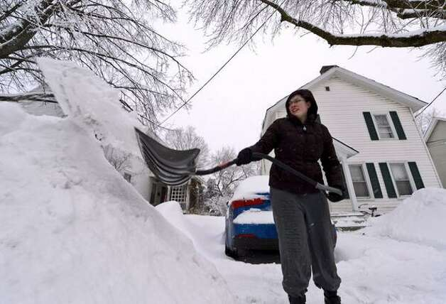 Alicia Citriniti moves some of the more than 12 inches of snow from her driveway on Morgan Avenue  in Glens Falls. (Skip Dickstein / Times Union)