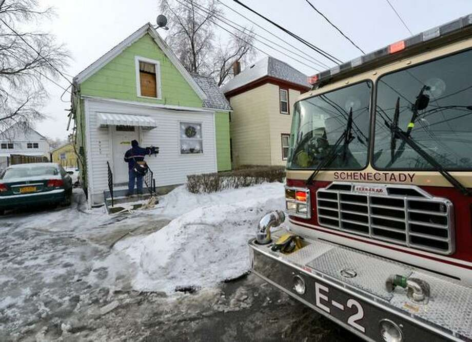 A letter carrier drops mail in the box at the scene of an early morn fire at 1336 Eighth Avenue in Schenectady. Fire caused extensive damage inside the building. (Skip Dickstein / Times Union)