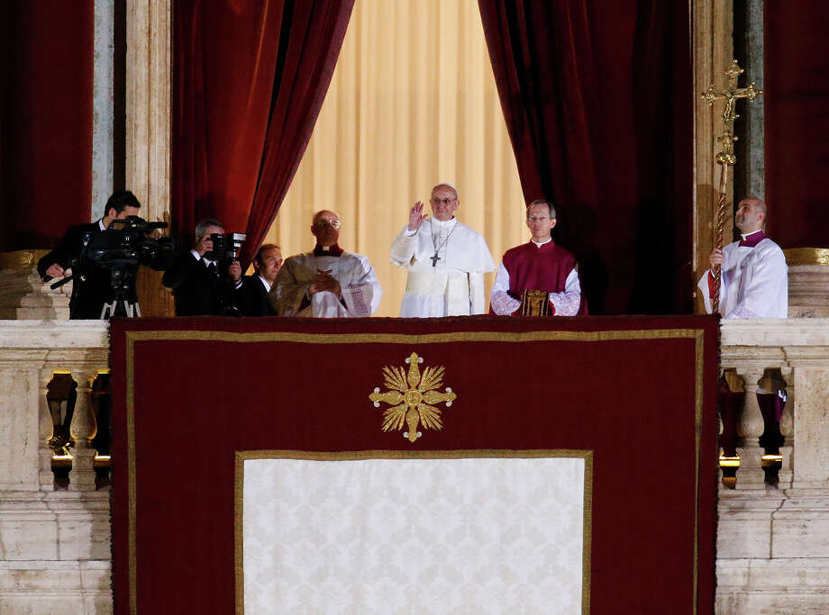 Pope Francis flanked by Monsignor Guido Marini, master of liturgical ceremonies, waves to the crowd from the central balcony of St. Peter's Basilica at the Vatican, Wednesday, March 13, 2013. Cardinal Jorge Bergoglio, who chose the name of Francis is the 266th pontiff of the Roman Catholic Church.  Photo: Michael Sohn, ASSOCIATED PRESS / The Associated Press2013