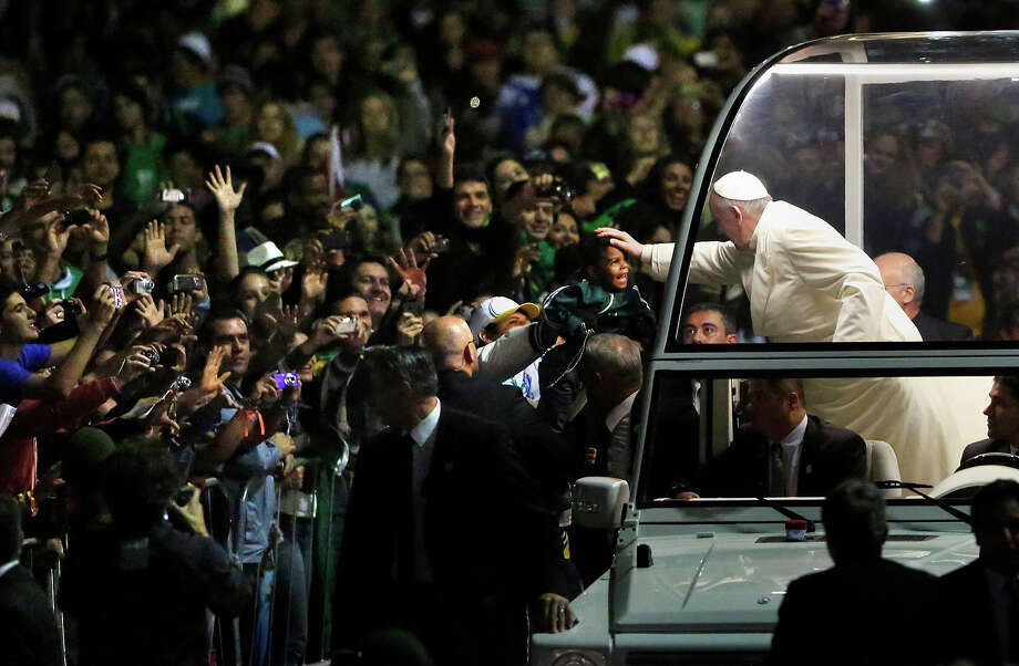 Pope Benedict blesses a child from his popemobile as he arrives for a vigil with pilgrims in Rio de Janeiro, Brazil, Saturday, July 27, 2013. Francis will preside over an evening vigil service on Copacabana beach that is expected to draw more than 1 million young people.  Photo: Jorge Saenz, ASSOCIATED PRESS / AP2013