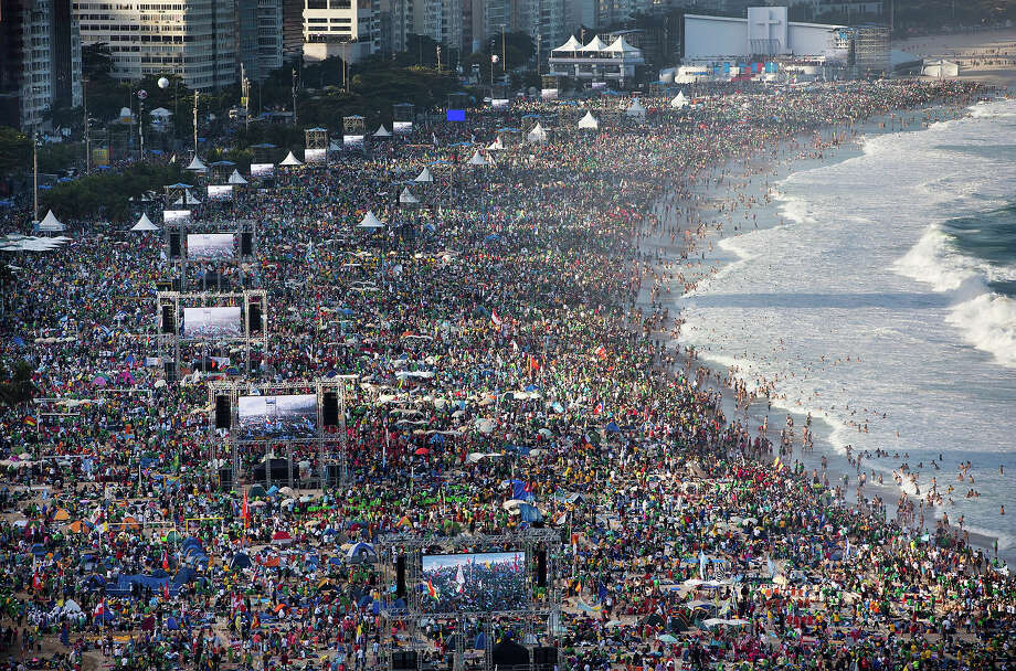 Pilgrims and residents gather on Copacabana beach before the arrival of Pope Francis for World Youth Day in Rio de Janeiro, Brazil, Saturday, July 27, 2013.  Francis will preside over an evening vigil service on Copacabana beach that is expected to draw more than 1 million young people.  Photo: Felipe Dana, ASSOCIATED PRESS / AP2013