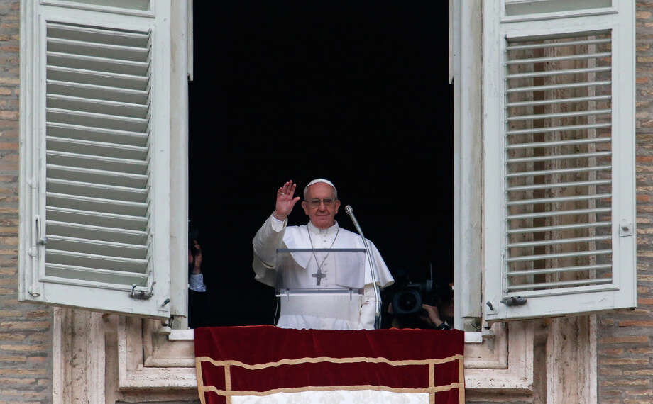 Pope Francis waves before delivering his Angelus prayer from the window of his studio overlooking St. Peter's Square, at the Vatican, Sunday, March 17, 2013.  Photo: Michael Sohn, ASSOCIATED PRESS / Kamera012013