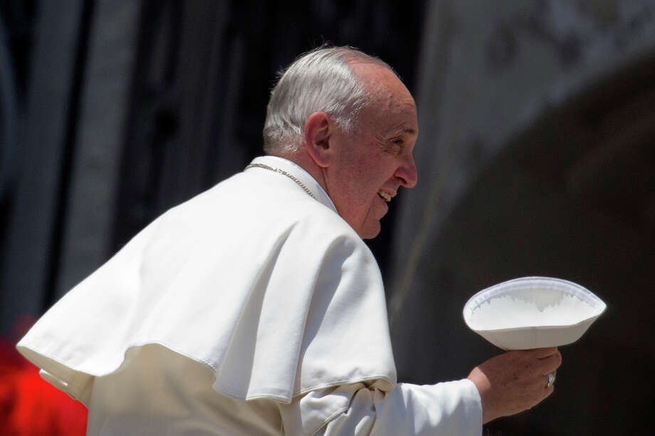Pope Francis holds his skull-cap as he leaves at the end of his weekly general audience, in St. Peter's Square, at the Vatican, Wednesday, May 29, 2013. The rain hasn't stopped Pope Francis. The 76-year-old pontiff, who lost part of a lung during his youth to an infection, got soaked Wednesday as he braved a brief spring shower to kiss babies and greet crowds at his weekly general audience in St. Peter's Square. Zooming around the piazza in his open-air jeep, Francis had no umbrella or cover over him as he made his way through a sea of brightly colored umbrellas, happily stopping to caress and kiss babies handed up to him.  Photo: Andrew Medichini, ASSOCIATED PRESS / AP2013