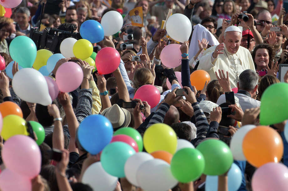 People wave balloons in front of Pope Francis as he is driven through the crowd ahead of his weekly general audience in St. Peter's Square, at the Vatican, Wednesday, Oct. 30, 2013. Photo: Alessandra Tarantino, ASSOCIATED PRESS / AP2013