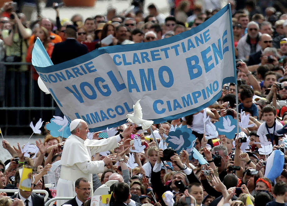 Pope Francis frees a dove as he is driven through the crowd in St. Peter's Square for his weekly general audience at the Vatican, Wednesday, May 15, 2013. As Francis toured the square in his open-topped popemobile at his Wednesday audience with the public, someone at the edge of the crowd thrust a white bird cage at him. Looking puzzled, his security detail took the cage, containing a pair of white doves, and handed it to Francis. Without hesitation, the pope opened the cage door, thrust a hand inside and extracted one dove, and with a flick of his hand, sent the bird flying over the square. Photo: Gregorio Borgia, ASSOCIATED PRESS / AP2013