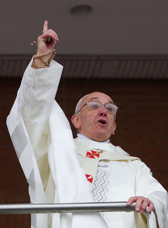 Pope Francis comments on the rain to pilgrims as he stands on a balcony at the Aparecida Basilica after celebrating Mass in Aparecida, Brazil, Wednesday, July 24, 2013.  Tens of thousands of faithful flocked to the tiny town of Aparecida, tucked into an agricultural region halfway between Rio de Janeiro and Sao Paulo, where he is to celebrate the first public Mass of his trip in a massive basilica dedicated to the nation's patron saint.  Photo: Domenico Stinellis, ASSOCIATED PRESS / AP2013