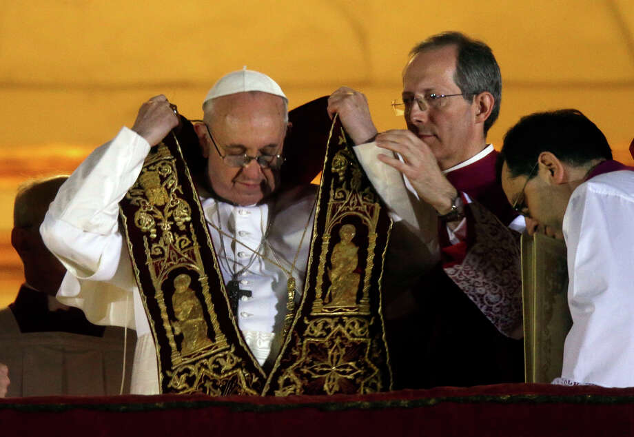 Pope Francis puts on his sash from the central balcony of St. Peter's Basilica at the Vatican, Wednesday, March 13, 2013. Cardinal Jorge Bergoglio who chose the name of  Francis, is the 266th pontiff of the Roman Catholic Church.  Photo: Gregorio Borgia, ASSOCIATED PRESS / AP2013
