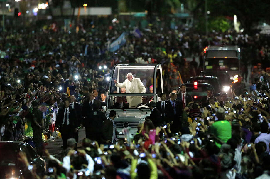Pope Benedict waves to people from his popemobile at the start of a vigil with pilgrims in Rio de Janeiro, Brazil, Saturday, July 27, 2013. Francis will preside over an evening vigil service on Copacabana beach that is expected to draw more than 1 million young people.  Photo: Jorge Saenz, ASSOCIATED PRESS / AP2013