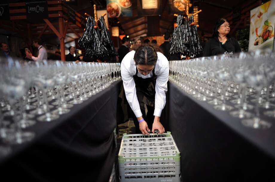 Daniel Gonzales of Treasure Island Job Core sets out wine glasses for guests at the entrance of the SF Chefs event held at Union Square in San Francisco, California Friday, August 2, 2013. Photo: Michael Short 2013, Special To The Chronicle