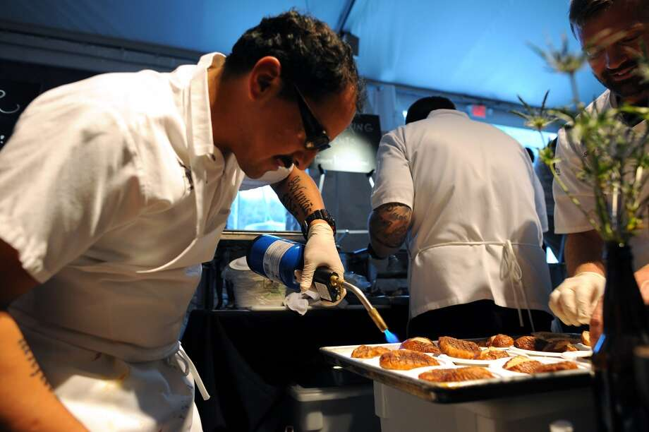 "Javier Montano uses a torch to sear the tops of ""pork 4 ways"" dishes at the Foxtail Catering booth during the SF Chefs event held at Union Square in San Francisco, California Friday, August 2, 2013. Photo: Michael Short 2013, Special To The Chronicle"