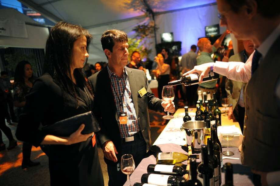 Jeanmarie Guenot(L) watches as Steve Sarver has a glass of wine poured for him at the Layer Cake Wines booth at the SF Chefs event held at Union Square in San Francisco, California Friday, August 2, 2013. Photo: Michael Short 2013, Special To The Chronicle