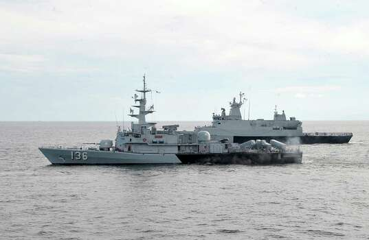 In this photo released by The Royal Malaysian Navy, Royal Malaysian Navy's missile corvette KD Laksamana Muhammad Amin, front, and Royal Malaysian Navy's offshore patrol vessel KD Selangor are seen during a search and rescue operation for the missing Malaysia Airlines plane over the Straits of Malacca, Malaysia, Thursday, March 13, 2014. Planes sent Thursday to check the spot where Chinese satellite images showed possible debris from the missing Malaysian jetliner found nothing, Malaysia's civil aviation chief said, deflating the latest lead in the six-day hunt. The hunt for the missing Malaysia Airlines flight 370 has been punctuated by false leads since it disappeared with 239 people aboard about an hour after leaving Kuala Lumpur for Beijing early Saturday. (AP Photo/The Royal Malaysian Navy) Photo: Associated Press / The Royal Malaysian Navy