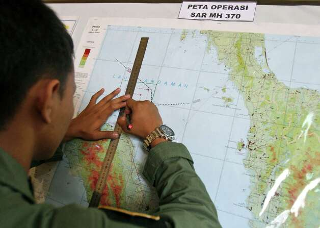An Indonesian Air Force officer draws a flight pattern flown earlier in a search operation for the missing Malaysia Airlines Boeing 777, during a post-mission briefing at Suwondo air base in Medan, North Sumatra, Indonesia, Thursday, March 13, 2014. The hunt for the missing jetliner has been punctuated by false leads since it disappeared with 239 people aboard about an hour after leaving Kuala Lumpur for Beijing early Saturday. (AP Photo/Binsar Bakkara) Photo: Binsar Bakkara, Associated Press / AP
