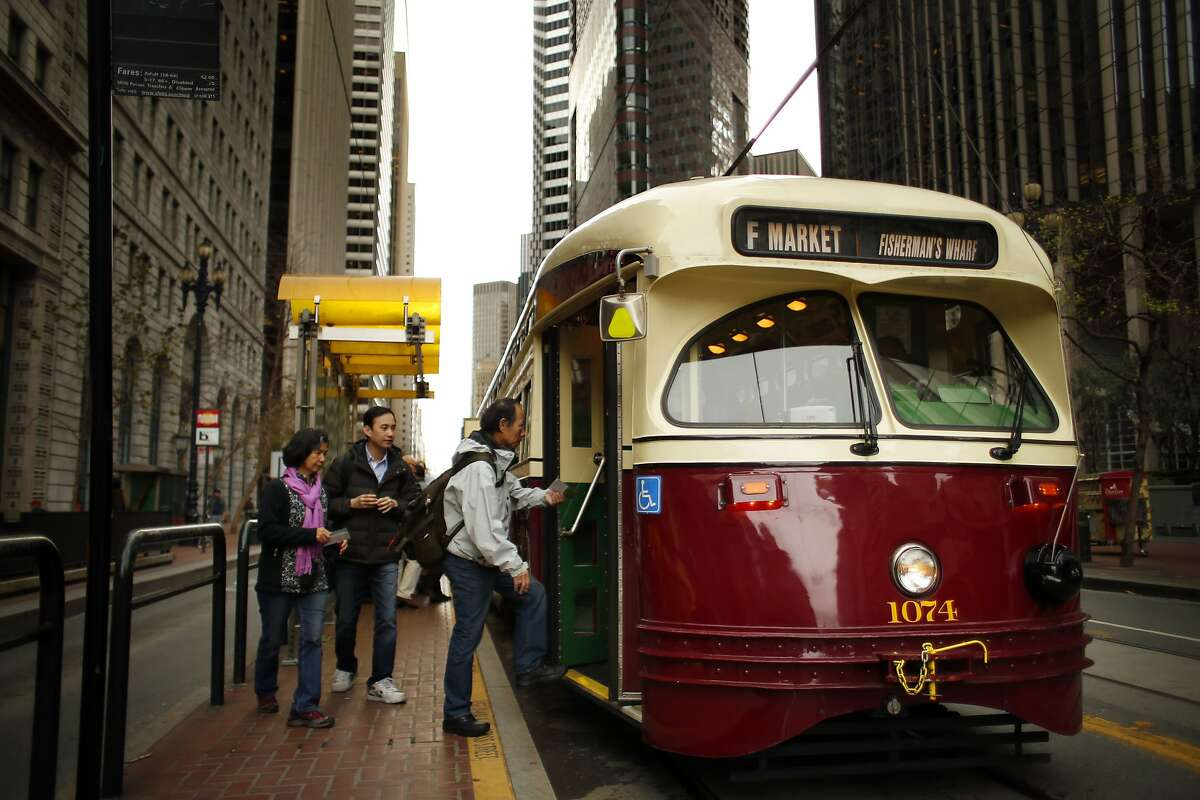 Passengers board an F Line Muni streetcar on Market Street in San Francisco, Calif., on Wednesday, March 5, 2014. Muni F Line of historic streetcars is popular with both tourists who tour the city and locals who use them for commute. But there is a suggestion that fares might go up to a premium rate of $6 like the Cable Cars, instead of the standard Muni $2 fare that is paid today.