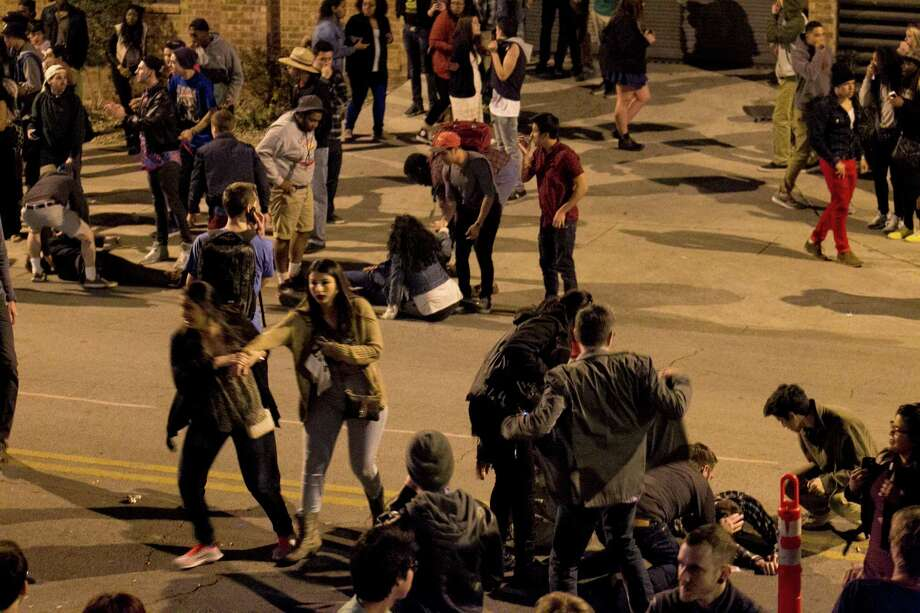 The crowd scatters seconds after several pedestrians were struck by a vehicle on Red River Street in downtown Austin, Texas, during SXSW on Wednesday March 12, 2014. Police say two people have died after a car drove through temporary barricades set up for the South By Southwest festival and struck a crowd of pedestrians. Photo: Jay Janner, AP Photo/Austin American-Statesman/Statesman.com / Austin American-Statesman