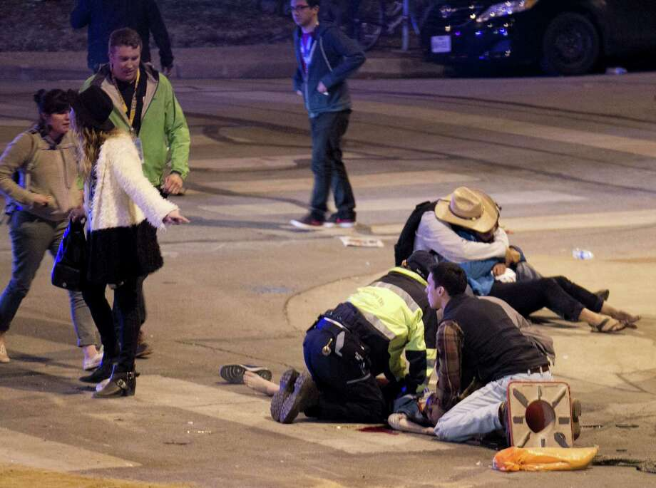 People perform CPR on a woman after she was struck by a vehicle on Red River Street in downtown Austin, Texas, at SXSW on Wednesday March 12, 2014. Police say a man and woman have been killed after a suspected drunken driver fleeing from arrest crashed through barricades set up for the South By Southwest festival and struck the pair and others on a crowded street. Photo: Jay Janner, AP Photo/Austin American-Statesman/Statesman.com / Austin American-Statesman