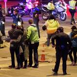 People walk away after the accident on Red River Street in downtown Austin, Texas, that left two dead at SXSW on Wednesday March 12, 2014. Police say a man and woman have been killed after a suspected drunken driver fleeing from arrest crashed through barricades set up for the South By Southwest festival and struck the pair and others on a crowded street.