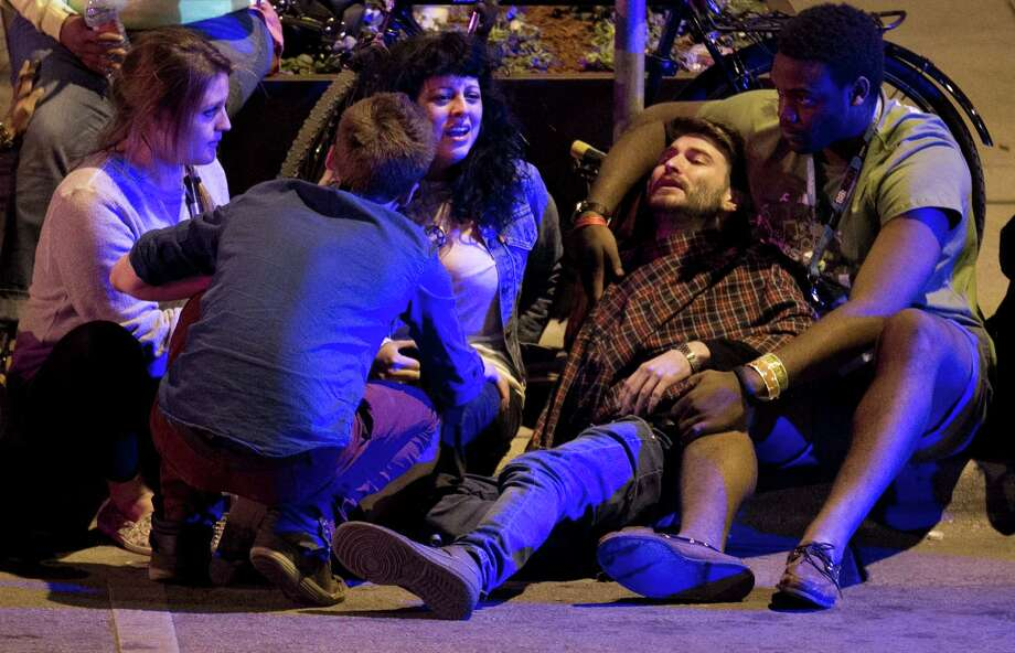 Unidentified people are comforted after being struck by a vehicle on Red River Street in downtown Austin, Texas, during SXSW on Wednesday March 12, 2014. Police say two people were confirmed dead at the scene after a car drove through temporary barricades set up for the South By Southwest festival and struck a crowd of pedestrians. Photo: Jay Janner, AP Photo/Austin American-Statesman/Statesman.com / Austin American-Statesman