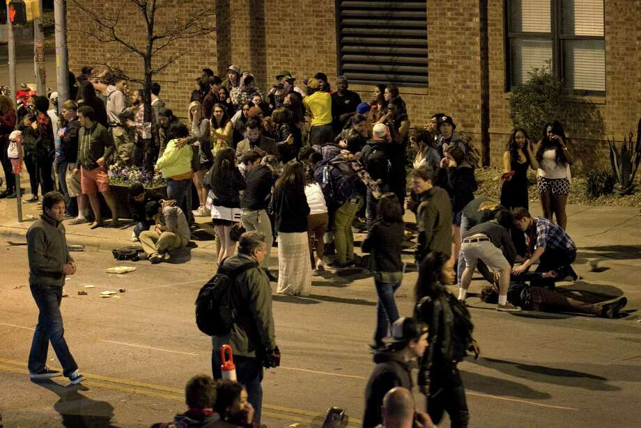People tend to those who were struck by a vehicle on Red River Street in downtown Austin, Texas, during SXSW on Wednesday March 12, 2014. Police say two people have died after a car drove through temporary barricades set up for the South By Southwest festival and struck a crowd of pedestrians. Photo: Jay Janner, AP Photo/Austin American-Statesman/Statesman.com / Austin American-Statesman